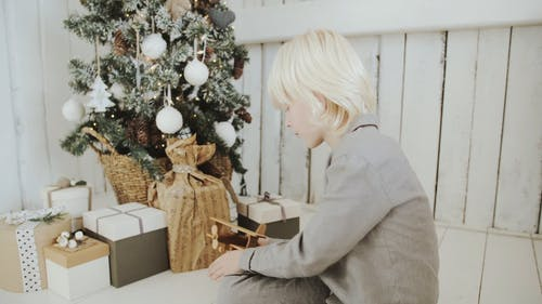 A Boy Playing His Airplane Toy Beside A Christmas Tree