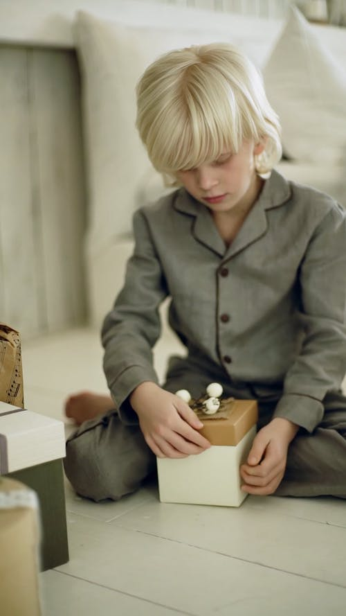 A Boy Trying To Open A Box Of Gift