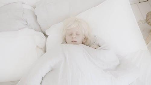 A Boy Lying In Bed To Sleep With A Teddy Bear Stuffed Toy