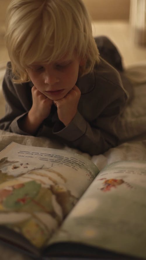 A Boy Reading A Book On A Bed