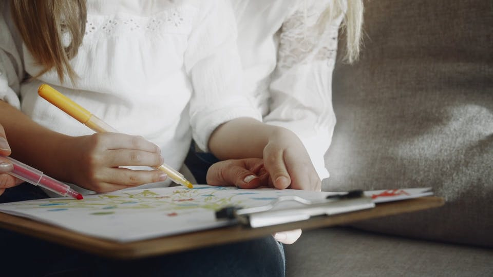 Mother And Daughter In Tandem Does Art Coloring On A White Paper