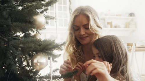 A Mother Assisting Her Daughter In Placing A Christmas Ball On A Christmas Tree