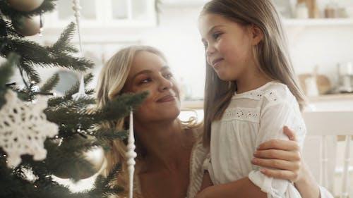 Мать и дочь счастливы, глядя на елку