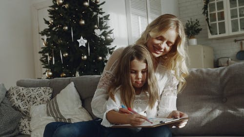 Mother And Daughter Bonding Together With A Background Of Christmas