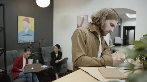 Two Women Having Conversation And A Man Writing Notes In The Office