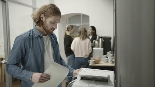 Man Using A Copying Machine In The Office