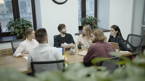 A Group Of People In A Business Meeting Looking And Talking About Documents In Discussion
