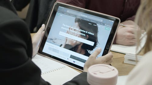 A Person Reviewing The Photos Stored In An Electronic Note Pad