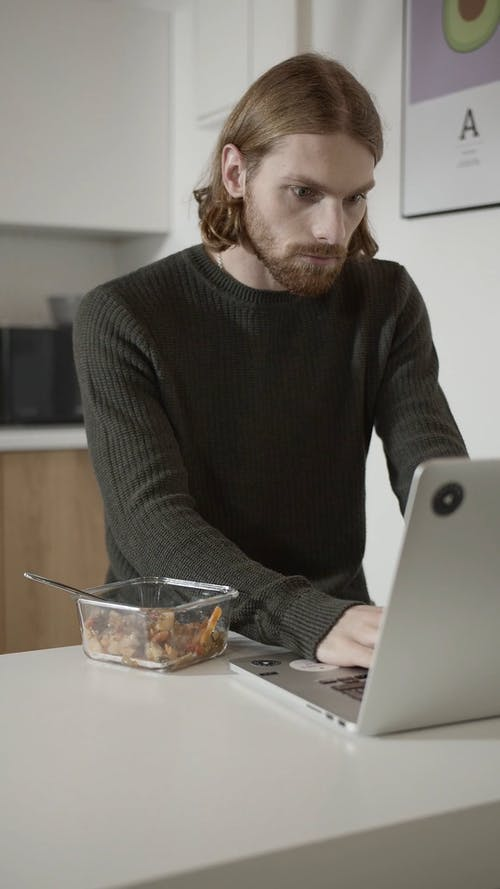 A Man Eating Breakfast While Working On A Laptop In The Office Pantry