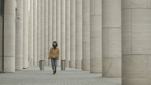 A Woman Walking Outside Of The Building Between Pillars