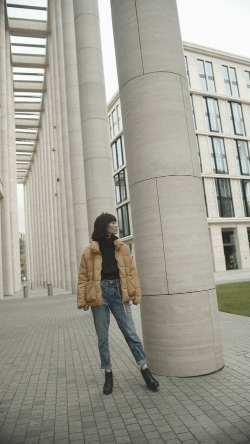 A Woman Standing Beside A Building Pillar Swaying Her Body