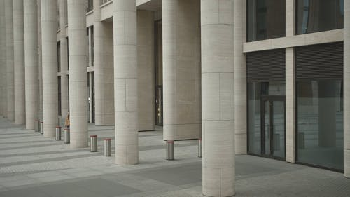 Woman Walking Outside A Building Of Pillars
