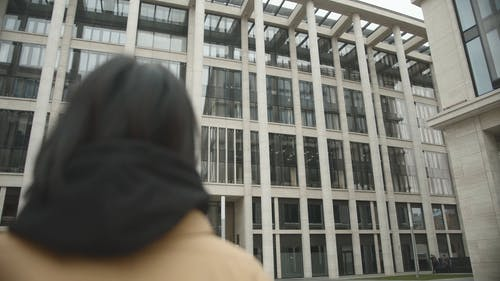 Woman Looking Around While Standing Outside A Building