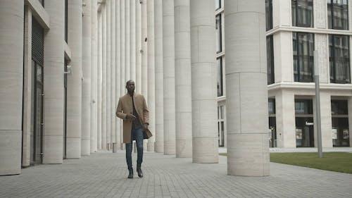 Man Walking Outside A Building