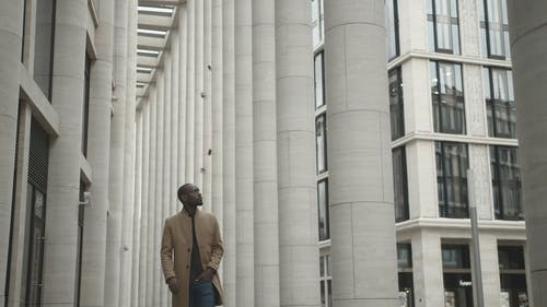 Man Looking Around While Walking Outside A Building