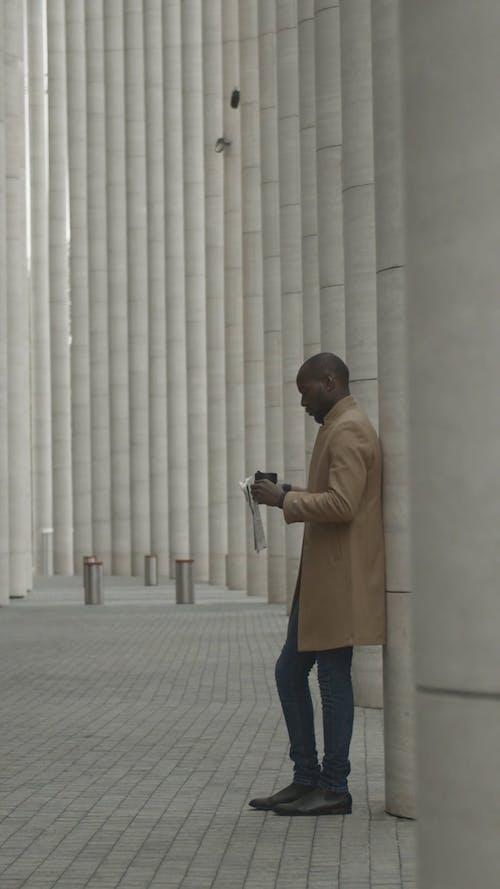 Мужчина с чашкой напитка и газетой на руках, опираясь на бетонный столб