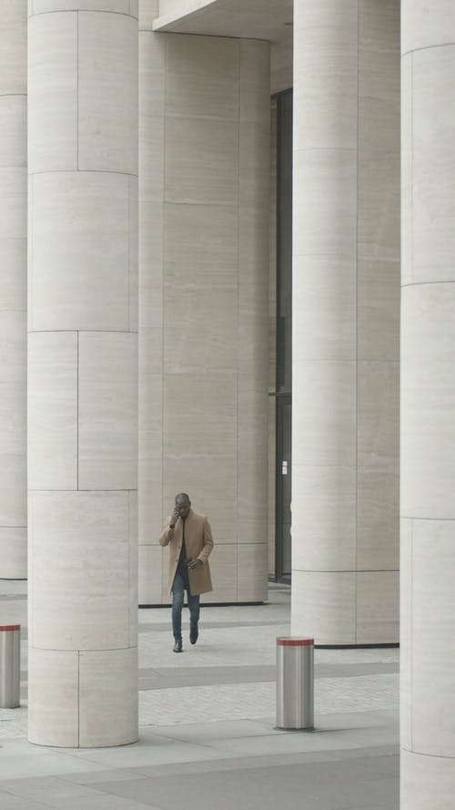 Man Walking Outside A Building Having A Conversation Over The Phone
