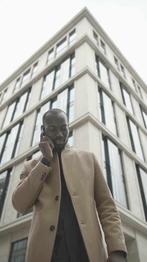 Man Outside A Building Having A Conversation With Someone Over The Phone