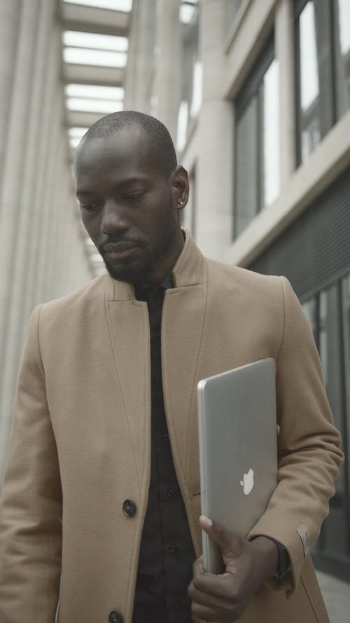 Man Wearing A Coat And Holding A Mac Book Pro