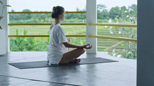 A Woman Meditating On A Platform Overseeing The Rice Field