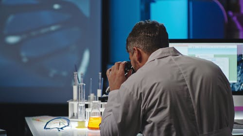 A Man On A Microscope Studying A Sample And Recording It In A Computer