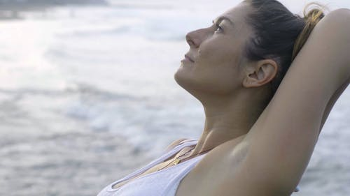 A Woman Doing Meditation And Stretching Exercise By The Beach
