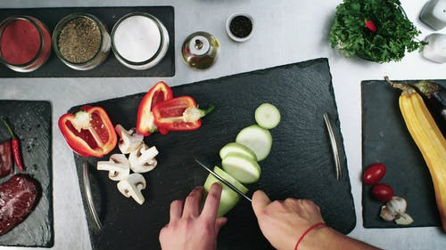 Cutting Vegetables To Pieces In A Chopping Board