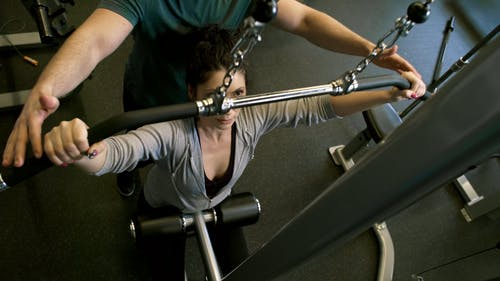 A Man Assisting A Woman In Using The Flat Pulldown Weights Equipment In A Gym