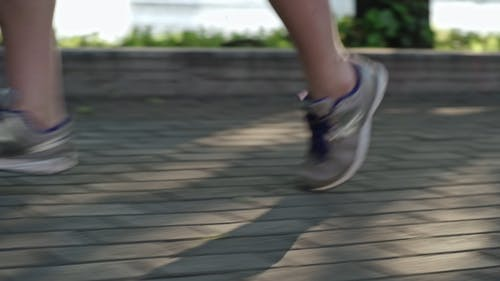 A Person Running On A Concrete Bricked Pavement