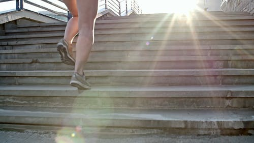 Backside Of A Woman Running Up An Outdoor Stairs