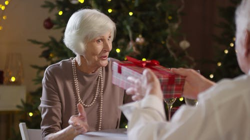 An Elderly Woman Showing Appreciation In Receiving A Gift From An Elderly Man
