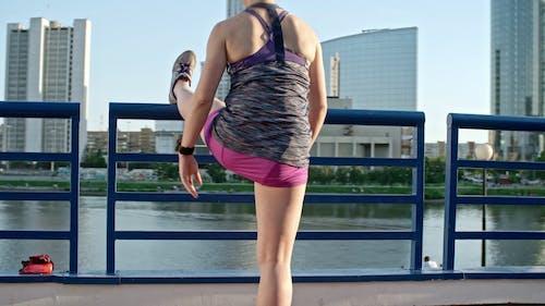 Kobieta Podnosząca Jedną Nogę Nad Poręczą Aby Wykonać ćwiczenia Rozciągające