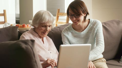 A Young Woman Teaching An Elderly Woman How To Use A Laptop