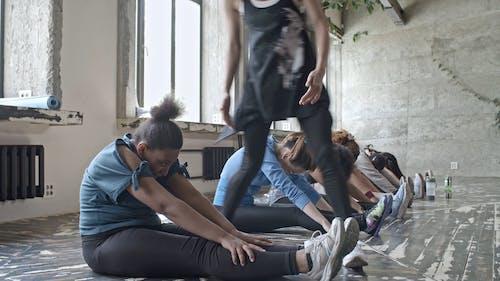 Kobieta Pomaga Innej Kobiety W Grupie Jej ćwiczenia Rozciągania I Zginania