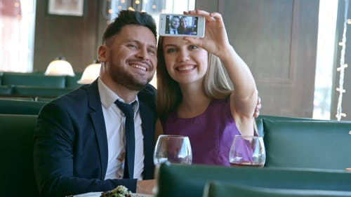 An Engaged Couple Taking A Video Of Themselves Using A Smartphone