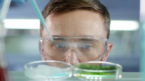 A Man In Deep Focus Of His Observation In An Experiment Being Undertaken