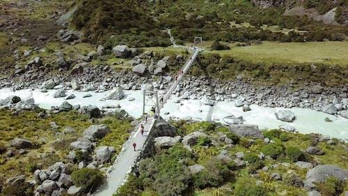 A Walk Bridge Built Over A Rocky River