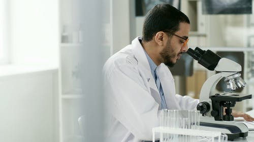 A Man Writing On Paper His Observation Of A Subject Under The Microscope