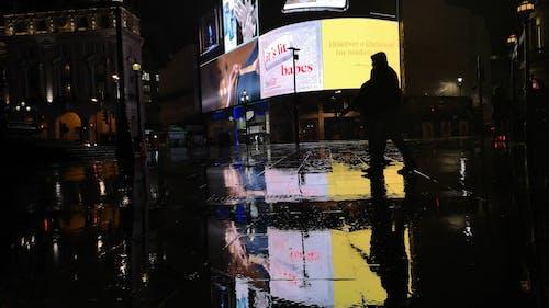 People Walking The Street Of London On A Rainy Night