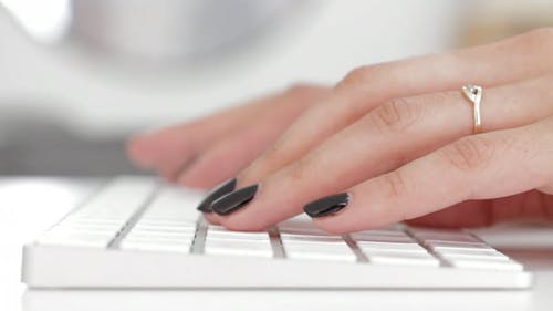 Person Fingers Busy Typing On A Keyboard
