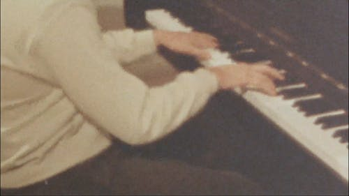 A Person Playing Music With A Piano