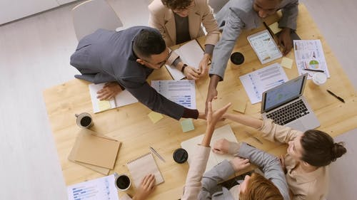 A Group Of People Shaking Each Others Hand In A Business Meeting