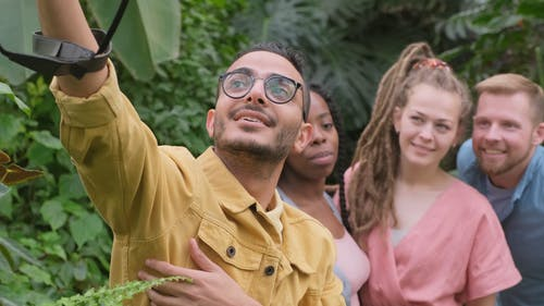 A Man Taking A Group Selfie In The Garden Park