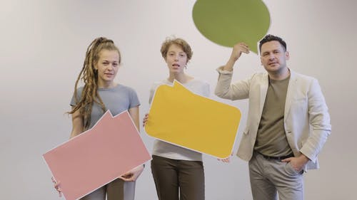 A Group Of People Lip Talking While Holding A Blank Statement Boards