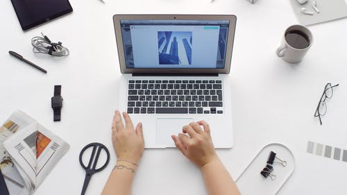 A Person Scrolling On Picture Images In A Laptop