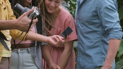 A Group Of People Looking At A Photo Taken From A Polaroid