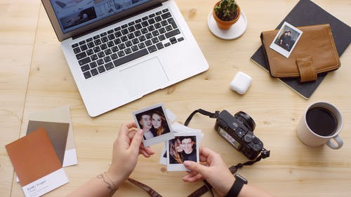 Person Holding Polaroid Photos