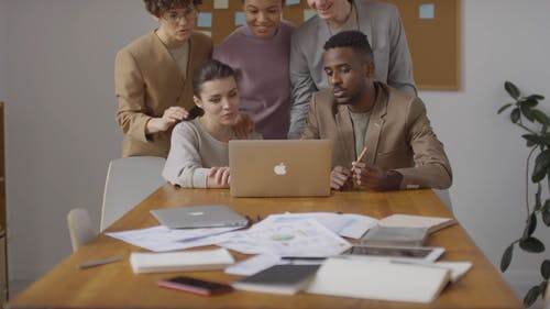 Group Of People Compressed Together Looking At A Laptop