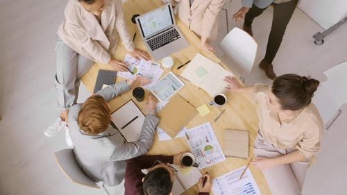 Group Of People Gathers Around A Table Working While Having Coffee