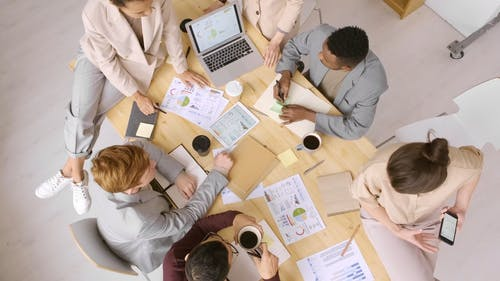 A Group Of People Discussing About Charts And Graphs In A Business Meeting